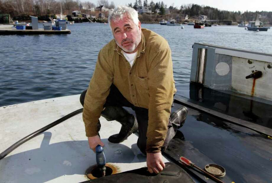 In this Tuesday, March 20, 2012 photo,  third generation lobsterman Craig Rogers  fuels up his lobster boat at Mackeral Cove in Bailey Island, Maine. Rogers, of Harpswell, said high fuel prices are the biggest concern of lobstermen today.(AP Photo/Pat Wellenbach) Photo: Pat Wellenbach