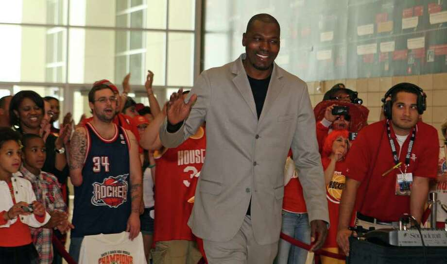 Former Houston Rockets player Hakeem Olajuwon waves to fans before the unveiling of a mural with the Houston Rockets team of the 1990s on Thursday, March 22, 2012, at the Toyota Center. Photo: James Nielsen, Chronicle / © 2012 Houston Chronicle