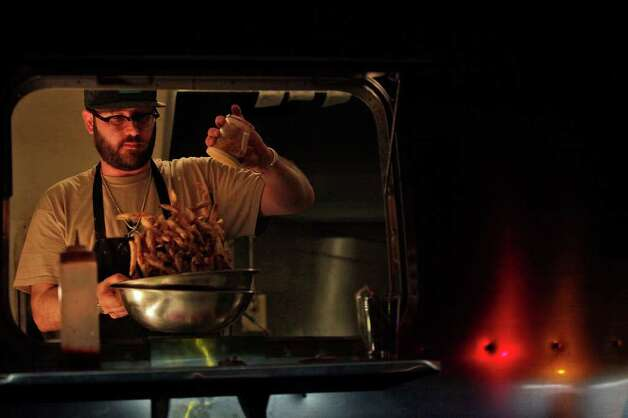taste - Owner Chris Cullum makes fries in the Attaboy Burgers Land Yacht parked at Alamo Street Eat Bar on Tuesday, March 20, 2012. LISA KRANTZ/San Antonio Express-News Photo: Lisa Krantz, San Antonio Express-News / @San Antonio Express-News