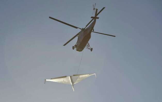 "A helicopter releases an 800-pound paper airplane for the Pima Air & Space Museum's ""Great Paper Airplane Project,"" on March 21, 2012 outside of Tucson, Ariz. Photo: BALFOUR_WALKER                      , Balfour Walker Photography / (c)BALFOURWALKER.COM"