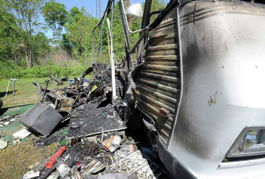 The remains of an RV fire are scattered on the lawn of the property on Reins Rd. in Beaumont, Friday, March 23, 2012. The fire was set by a distraught suicidal woman. Tammy McKinley/The Enterprise Photo: TAMMY MCKINLEY