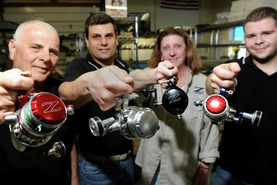 From left, John Posh, Ron DiCostanzo, Wendy Scaia and Devin LeConte hold ZeeBaaS fishing reels at the company's facility in Stratford, Conn. March 23rd, 2012. Photo: Ned Gerard / Connecticut Post