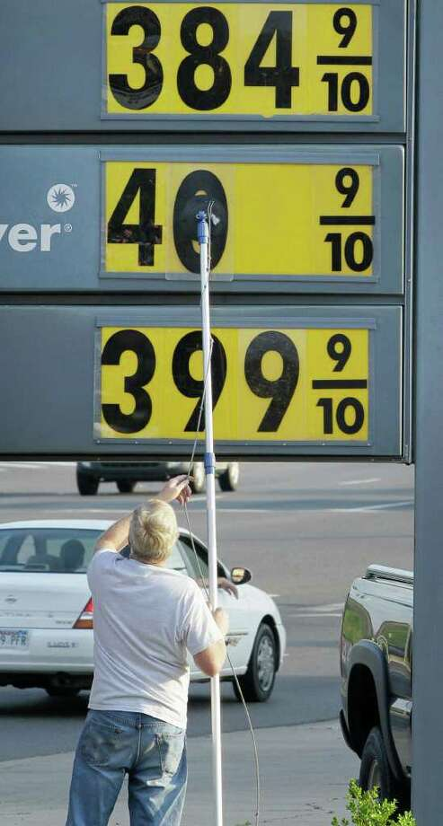 In this March 19, 2012 photo, a man changes advertised fuel prices at a Shell station in Hot Springs, Ark.  Americans have pumped less gas every week for the past year. During those 52 weeks, gasoline consumption dropped by 4.2 billion gallons, or 3 percent, according to MasterCard SpendingPulse. The decline is the longest since a 51-week period during the recession. (AP Photo/Danny Johnston) Photo: Danny Johnston / AP