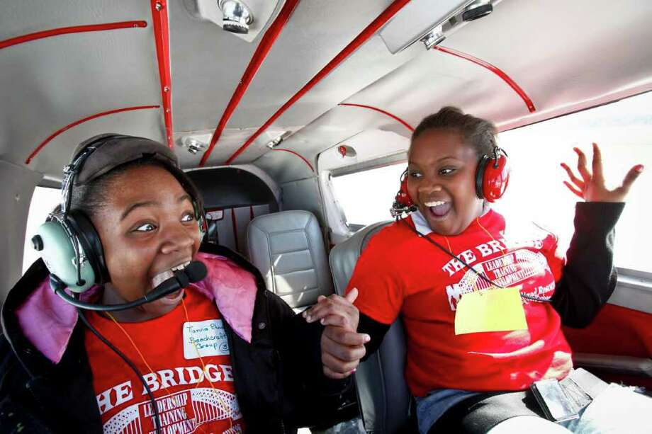 Tianna Rhodes, 11, and Tylandria Harrison, 11, react to what is their first flight ever, as the Piper Cherokee Six aircraft flown by Chris Prause takes off from the runway at the Houston Southwest Airport, Saturday, Feb. 12, 2011, in Rosharon. Forty kids from the troubled Haverstock apartment complex were bussed to the Texas Taildraggers flight school where they took a 20 minute ride in the sky in the hopes they see life beyond the gates of their home. Photo: Michael Paulsen, Houston Chronicle / Houston Chronicle