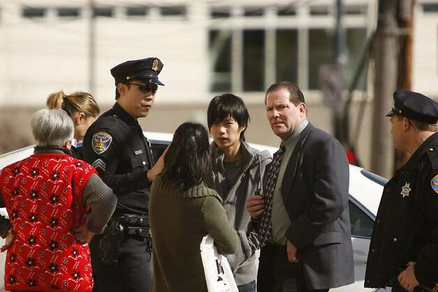 Chan-Fong Lin (center, back to camera) talks with SFPD and neighbors on Howth Street in San Francisco, where 5 bodies were found. Photo: Siana Hristova, The Chronicle