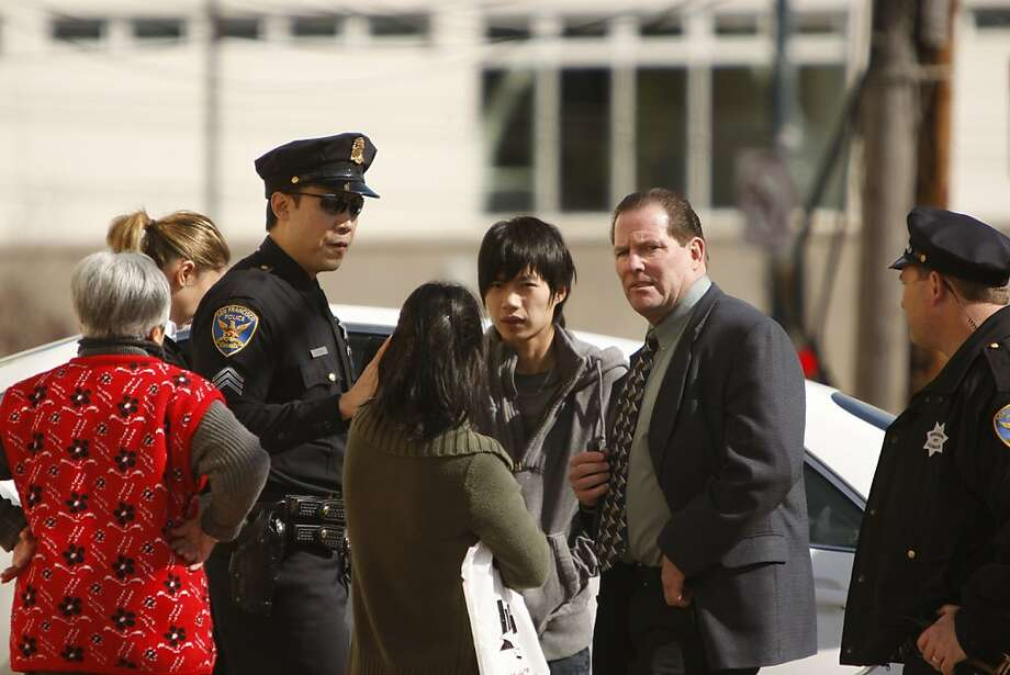Officials talk to Chan-Fong Lin (center, back) and other residents on Howth St. near City College of San Francisco on Friday, March 23. Police have made an arrest in five grisly slayings in a quiet San Francisco neighborhood. Photo: Siana Hristova, The Chronicle