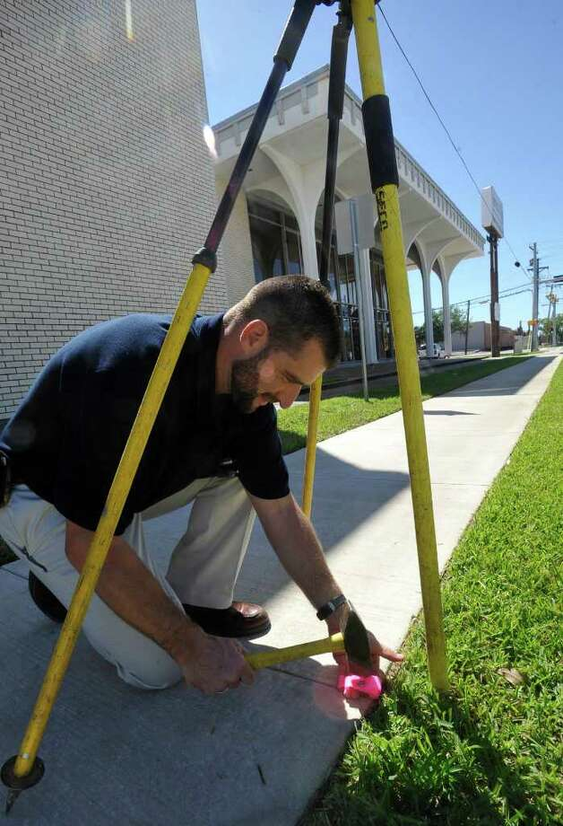 Dax Sutherland, Survey Supervisor for Mark W. Whiteley and Associates Incorporated, pounds a Mag Nail into the sidewalk outside the American Office Commercial Office Furniture Building. He had used a GPS unit to locate the coordinates, given to him by Tom Rowe,  of the geographic center of Beaumont as of Thursday afternoon.  Sutherland determined, the spot was actually down Fannin Street, 191.8 feet from the centerline of 11th Street and 34.37 feet south of where he is pounding, inside the American Office Furniture building behind him.  Dave Ryan/The Enterprise Photo: Dave Ryan