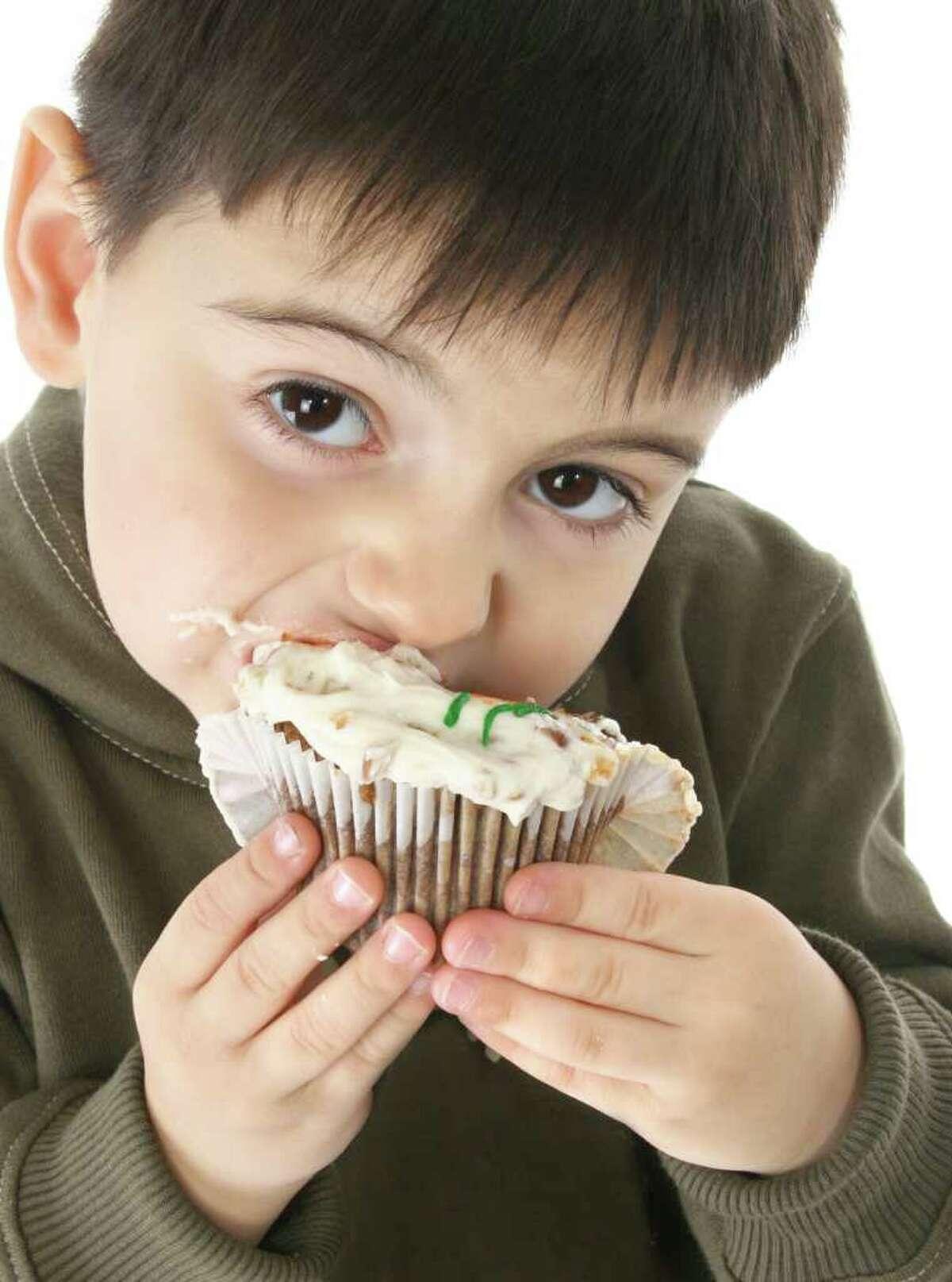 Three year old boy eathing iced carrot cake cupcake.