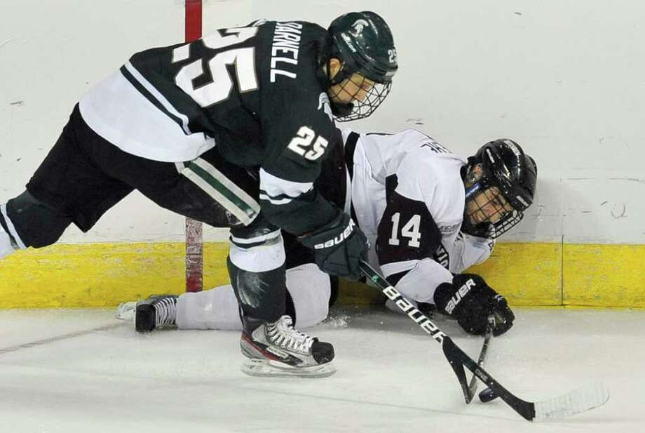 Michigan State's Brent Darnell, left, and Union College's Shayne Gostisbehere, right, fight for control of the puck during the second period of an East regional semifinal game in the NCAA college hockey tournament in Bridgeport, Conn., Friday, March 23, 2012. (AP Photo/Jessica Hill) Photo: Jessica Hill
