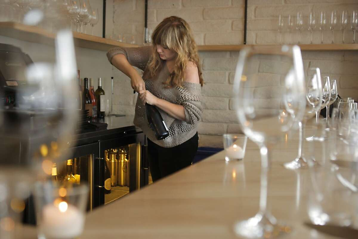 Sarah Elliot opens a bottle before she serves wine to customers at Commonwealth restaurant in San Francisco, Calif., on Tuesday, March 20, 2012.