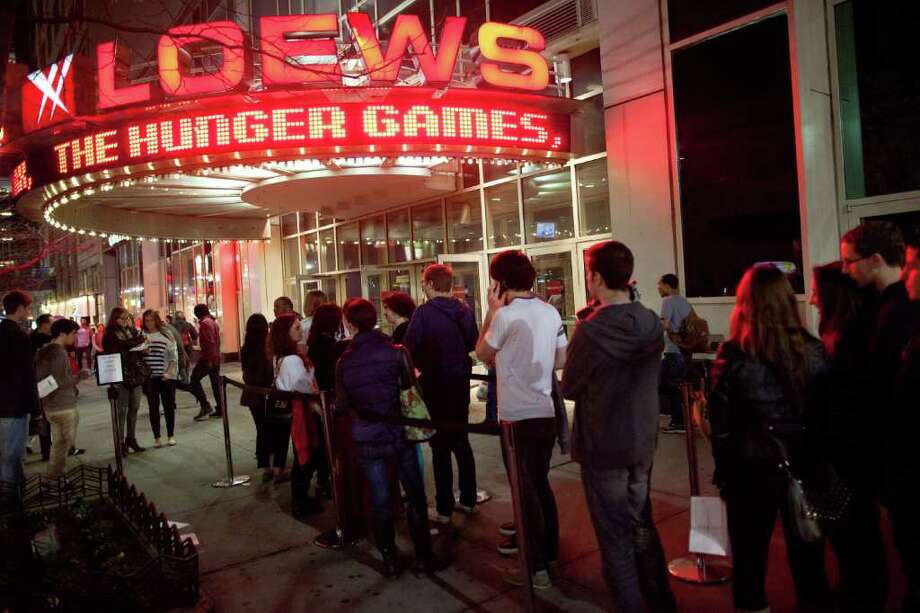 """Fans line up to see the midnight shows of """"The Hunger Games,"""" at the 34th Street Loews AMC Theatre, Thursday, March 22, 2012, in New York. The film, about children who are forced to compete in a live televised death match in the not-too-distant future, is based on the popular young adult book series by Suzanne Collins. (AP Photo/John Minchillo) Photo: John Minchillo"""