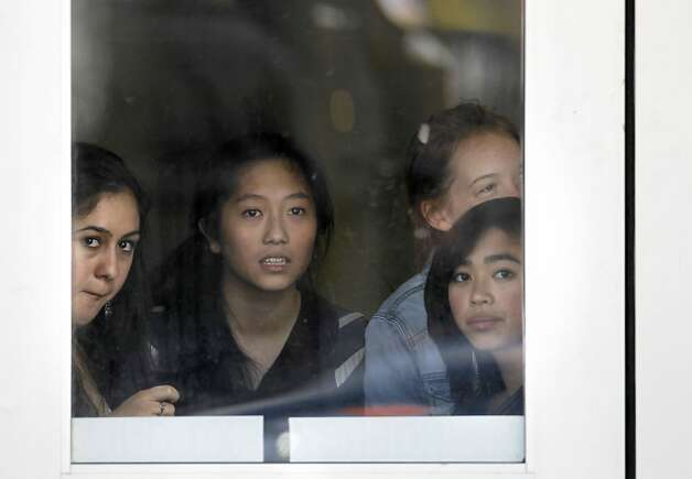 Students at nearby Lick-Wilmerding High School watch the police investigation through a window. Photo: Michael Macor, The Chronicle