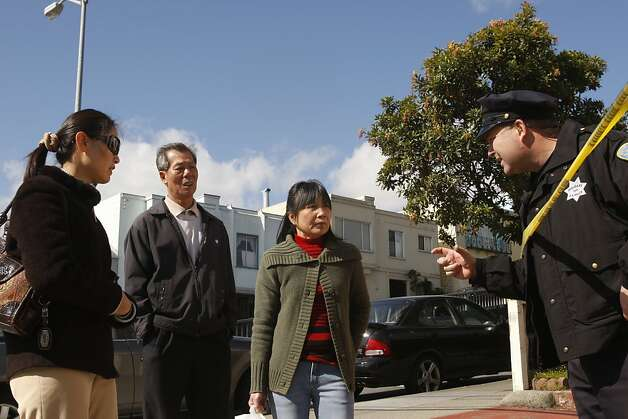 A police officer asks Huan Ruixu, center, and Chan-Fong Lin (right) for ID to let them pass beyond the yellow tape to their house in the neighborhood. Five people were found dead at 16 Howth Street near City College in San Francisco, Ca. Photo: Siana Hristova, The Chronicle