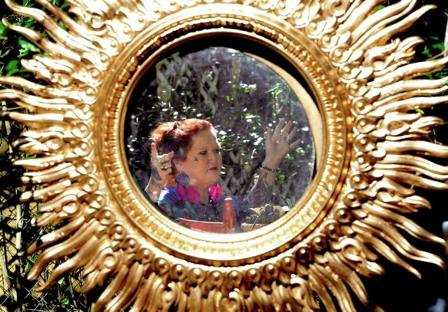 """Patricia """"Patches"""" Droddy, while sitting in her front yard enjoying the peace and quiet of her """"Mystic Woods of Whispering Spirits"""" that she has created, is reflected in one of the many mirrors that hang from the tree and bush branches.  Her home and the gardens around it are an ongoing art project, even after 20 years.  Dave Ryan/The Enterprise Photo: Dave Ryan"""