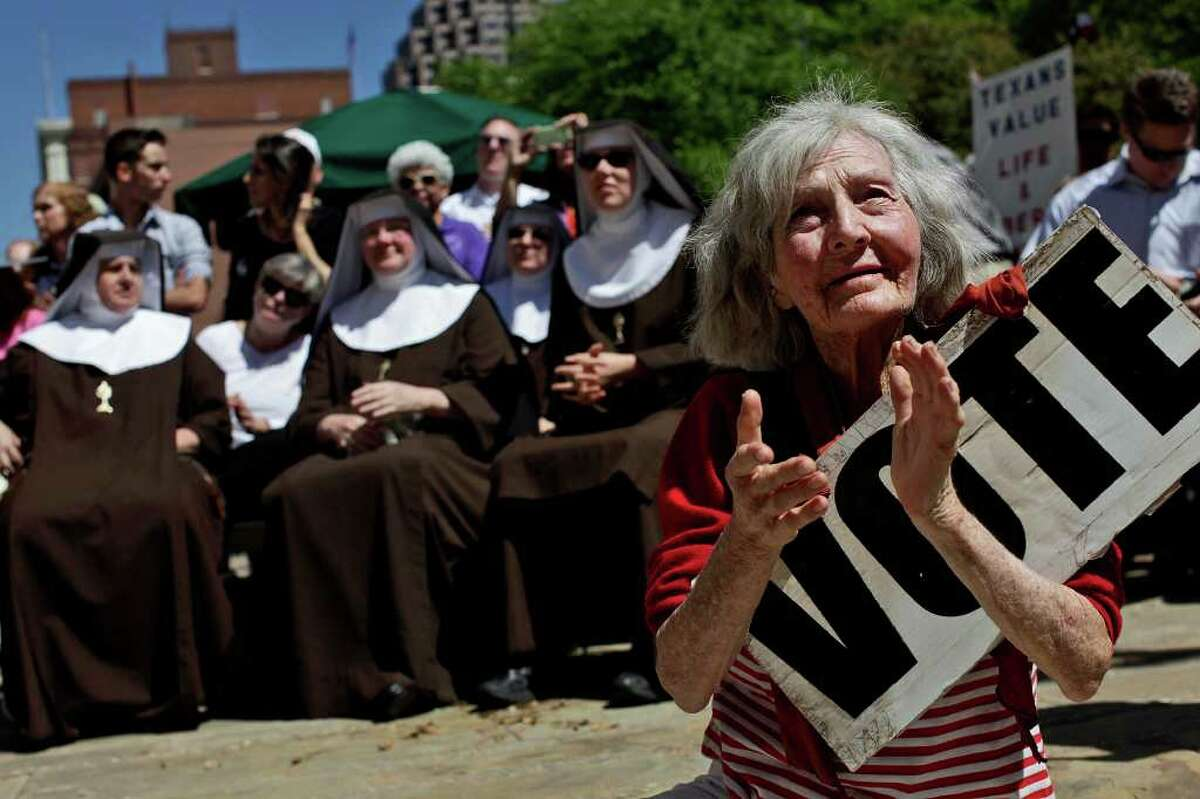 metro - Tessye Maurer applauds a speaker's remarks as she sits in front of a group of Poor Clare Nuns of Perpetual Adoration during the Stand Up for Religious Freedom Rally on Main Plaza in front of San Fernando Cathedral on Friday, March 23, 2012. LISA KRANTZ/San Antonio Express-News