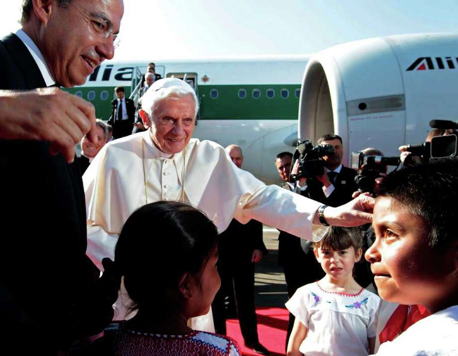 Mexico's President Felipe Calderon, left,  looks on as Pope Benedict XVI is greeted by children at the airport in Silao, Mexico, Friday March 23, 2012. Benedict's weeklong trip to Mexico and Cuba is his first to both countries. Photo: Gregorio Borgia