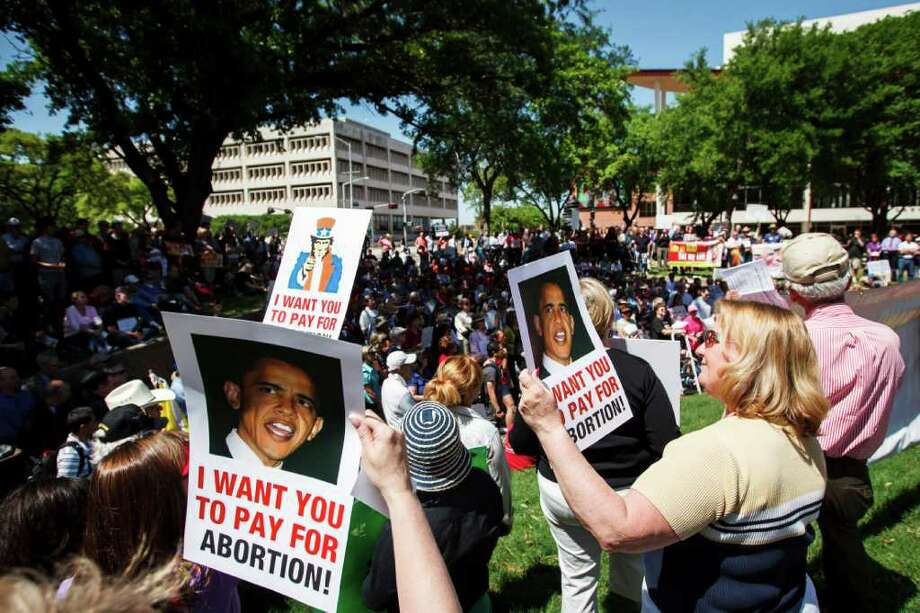 Event participants hold signs during the Stand Up for Religious Freedom rally where hundreds of Catholics and others opposed to an Obama administration requirement that religious employers provide birth control coverage gather at Tranquility Park. Photo: Michael Paulsen, Houston Chronicle / © 2012 Houston Chronicle