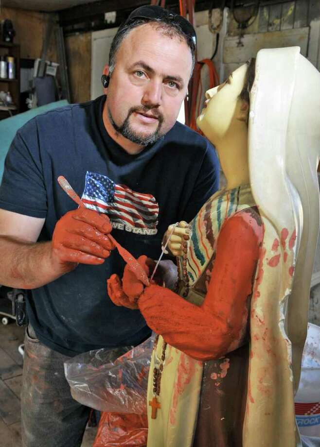 Artur Matia of Matia Historic Restoration restores a century-old statue of St Bernadette from St. Anne's chuch in Watervliet at his Alplaus studio Thursday March 22, 2012.   (John Carl D'Annibale / Times Union) Photo: John Carl D'Annibale / 00016909A