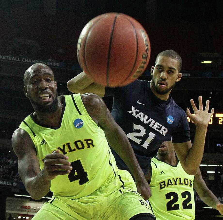 Baylor's Quincy Acy (4) and Xavier's Jeff Robinson (21) vie for a lose ball as Baylor's A.J. Walton looks on during the second half of an NCAA tournament South Regional semifinal college basketball game Friday, March 23, 2012, in Atlanta. (AP Photo/John Bazemore) Photo: John Bazemore, Associated Press / AP