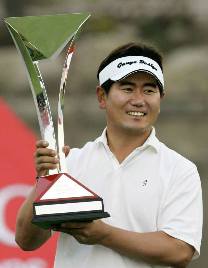 South Korean golfer Yang Yong-eun holds the trophy after winning the HSBC Champions golf tournament Sunday, Nov. 12, 2006 at Sheshan Golf Club in Shanghai, China. Yang won the tournament with score of 14-under 274.  (AP Photo/Kin Cheung) Photo: KIN CHEUNG / AP