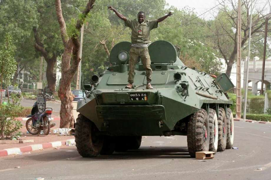 A soldier poses atop a military vehicle, as it stands guard outside the presidential palace following a military coup in Bamako, Mali, Friday, March 23, 2012. The whereabouts of Mali's president Amadou Toumani Toure were unknown Friday, a day after mutinous soldiers declared a coup, raising fears and prompting uncertainty in a West African nation that had been one of the region's few established democracies. (AP Photo/Harouna Traore) Photo: Harouna Traore / AP