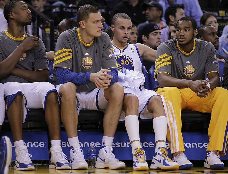 Golden State Warriors' Stephen Curry (30) sits on the bench beside Andris Biedrins, second from left, during the second half of an NBA basketball game against the Memphis Grizzlies Wednesday, March 7, 2012, in Oakland, Calif. (AP Photo/Ben Margot) Photo: Ben Margot, Associated Press