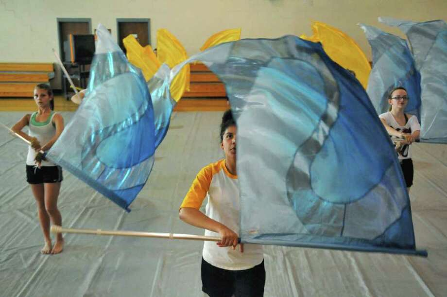 Paige DeLond, 14, left, Morgan Heyward, 15, center, and Amanda Eichenhofer, 12, right, all of Albany, and fellow members of the Albany Falcons Winter Guard rehearse at the Albany School of Humanities on Tuesday evening March 20, 2012 in Albany, N.Y. The guard is in their second season, and is hosting a competition on Saturday.   (Philip Kamrass / Times Union ) Photo: Philip Kamrass / 00016894A