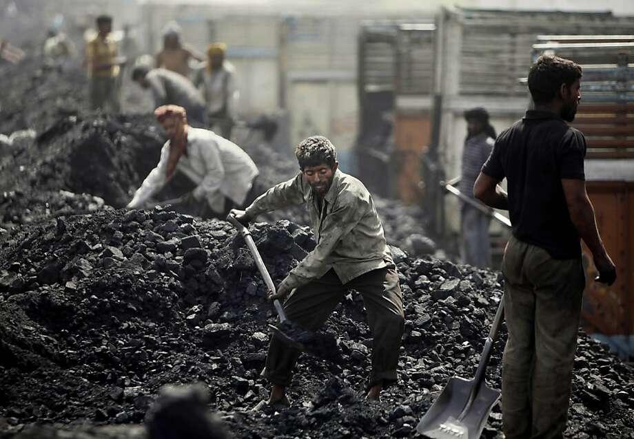 Indian laborers load coal onto trucks at a coal depot on the outskirts of Jammu, India, Friday, March 23, 2012. India's scandal-plagued government lost hundreds of billions of dollars by selling coalfields to companies without competitive bidding, according to a leaked audit report that the auditor itself called misleading. Angry lawmakers blocked proceedings in Parliament on Thursday, March 22, 2012, after the findings by India's Comptroller and Auditor General were printed by The Times of India newspaper. (AP Photo/Channi Anand) Photo: Channi Anand, Associated Press