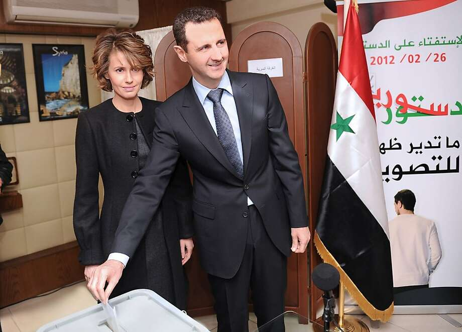 In this Sunday Feb. 26, 2012 file photo released by the Syrian official news agency SANA, Syrian President Bashar Assad casts his ballot next to his wife Asma at a polling station during a referendum on the new constitution, in Damascus, Syria. As Syria's bloodshed deepens, the country's British-born first lady has become an object of contempt for many, a Marie Antoinette figure who shopped online for fondue sets and 6-inch, crystal-encrusted Christian Louboutin heels while her country burned. The EU has slapped sanctions on Asma Assad, the young, stylish wife who for a decade offered a veneer of respectability to one of the world's most secretive and ruthless dictatorships. Photo: Anonymous, Associated Press