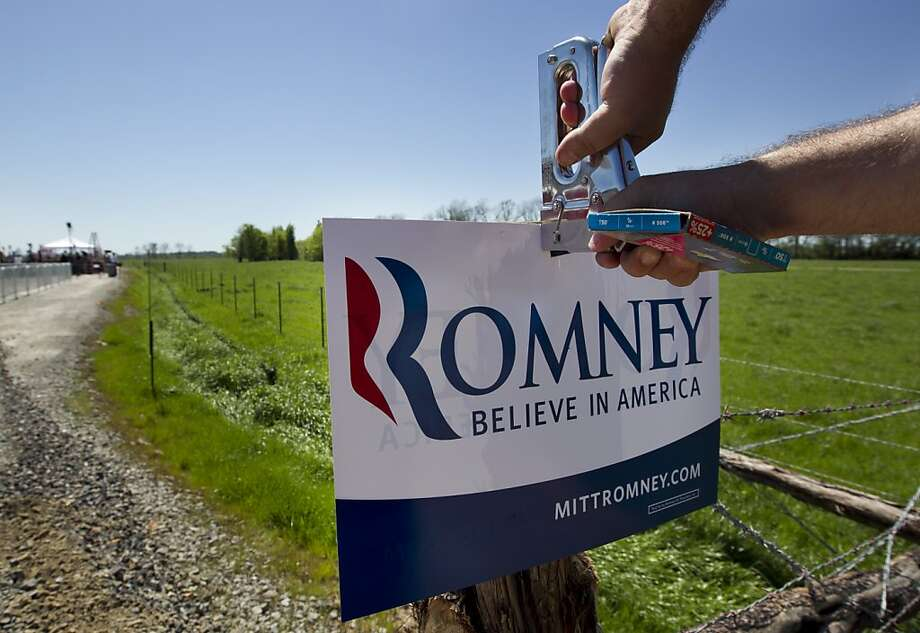 A campaign worker staples a placard to a post before campaign event for Republican presidential candidate, former Massachusetts Gov. Mitt Romney in Shreveport, La., Friday, March 23, 2012. Photo: Steven Senne, Associated Press