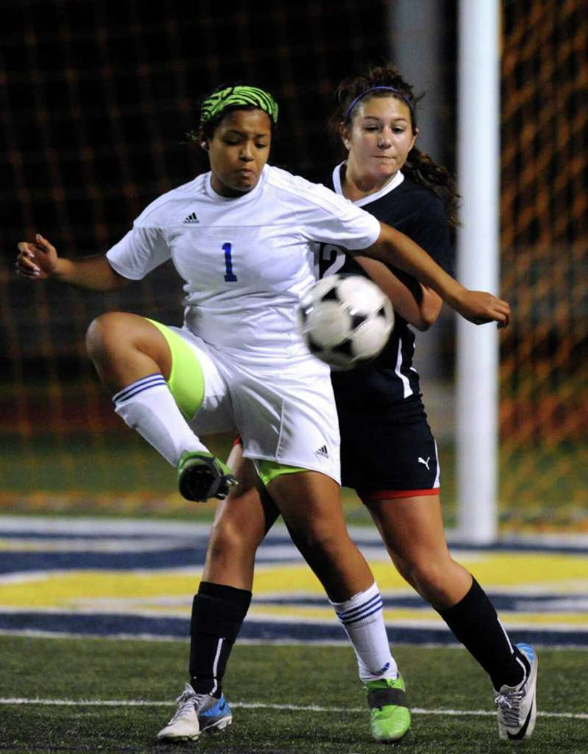 Mickey Garcia (1) of Clemens kicks the ball as Mikaylah Collins of Smithson Valley defends during girls soccer action at Clemens High School on Friday, March 23, 2012. Billy Calzada / San Antonio Express-News