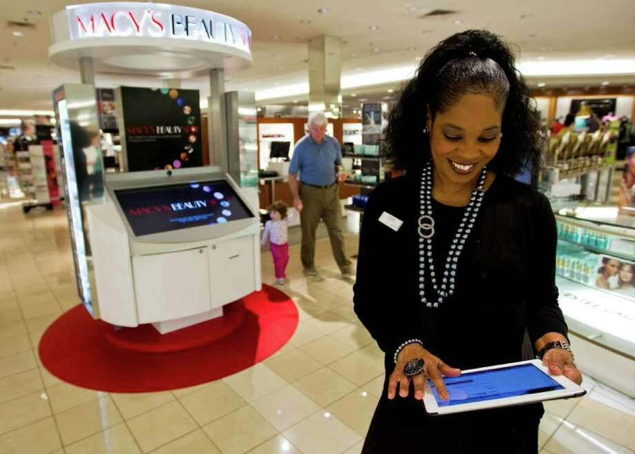 """Pamela Floyd, a beauty department concierge at Macy's in the Memorial City Mall, uses her iPad to see what a customer may want to explore. She helps shoppers use the """"Beauty Spot,"""" at left, which lets customers compare various beauty product choices. Photo: Nick De La Torre / © 2012  Houston Chronicle"""