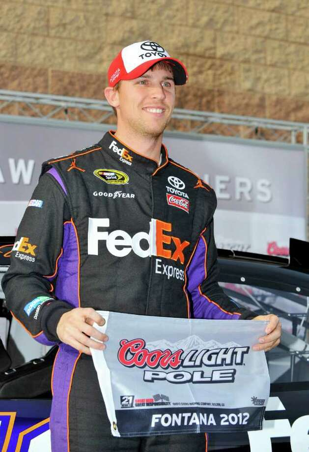 Denny Hamlin holds up the pole award for finishing on top after qualifying for Sunday's NASCAR Sprint Cup Series Auto Club 400 auto race, Friday, March 23, 2012, in Fontana, Calif. (AP Photo/Autostock, Nigel Kinrade) Photo: Nigel Kinrade / AP2012