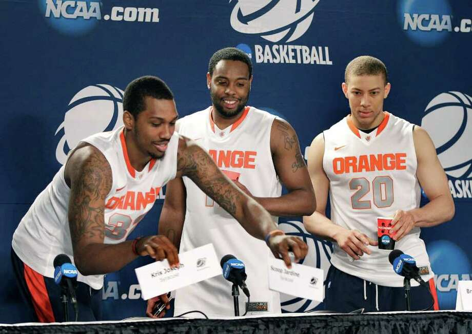 Syracuse's Kris Joseph, left, rearranges the name plates for himself and Scoop Jardine, center, as Brandon Triche, right, watches at the start of a news conference in Boston, Friday, March 23, 2012. Syracuse will play Ohio State in an NCAA tournament East Regional final college basketball game on Saturday. (AP Photo/Elise Amendola) Photo: Elise Amendola