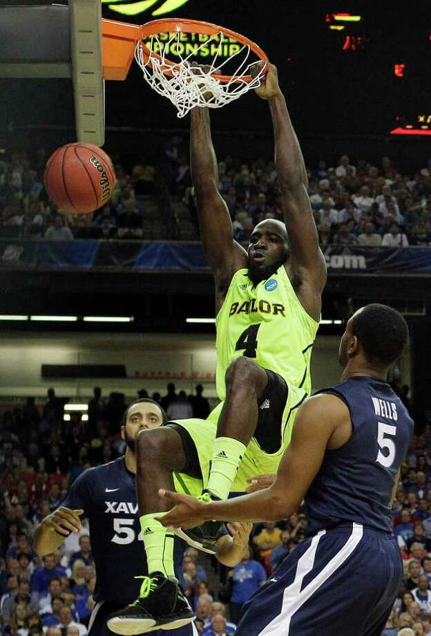 Baylor's Quincy Acy (4) dunks the ball as Xavier's Dezmine Wells, right, and Xavier's Andre Walker look on during the second half of an NCAA tournament South Regional semifinal college basketball game Friday, March 23, 2012, in Atlanta. (AP Photo/John Bazemore) Photo: John Bazemore