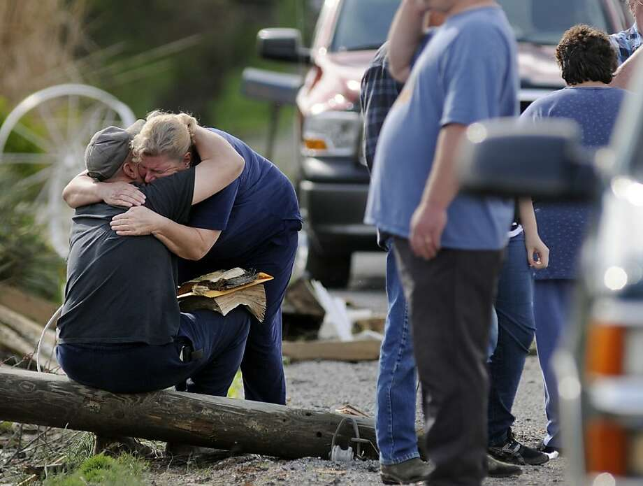 Loved ones embrace at the scene of a deadly tornado that touched down Friday, March 23, 2012 near Opdyke in Jefferson County, Ill. Pat Brown, 60, was killed and a second person injured when Brown's double-wide trailer was lifted off the ground by the funnel cloud and dropped on the opposite side of the road. (AP Photo/Alan Rogers, The Southern Illinosian) Photo: Alan Rogers, Associated Press
