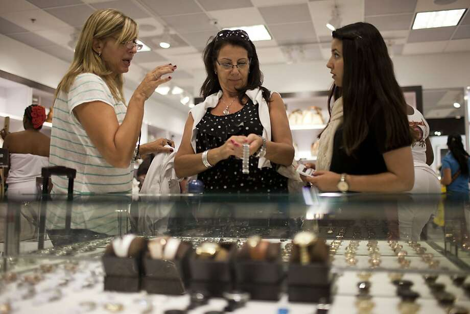 Beatriz Cesari, center, and her friend Sylvia Schleier, left, both from Sao Paulo, talk to sales woman Marina Vacanti, also from Brazil, as they shop in Miami, Florida, Sunday March 4, 2012. Brazilian travelers spend more per capita than any other visitors to the U.S.  (AP Photo/Felipe Dana) Photo: Felipe Dana, Associated Press