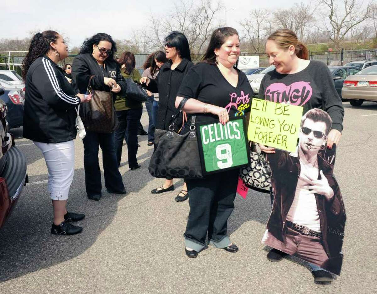 Melanie DiVasta, center, of Boston, and friend, Lindsay Gray, right, of New Hampshire, wait in line to see the New Kids on the Block, the boy band that enjoyed their greatest success in the late 1980s and early 1990s, at the Arch Street teen center in Greenwich, Saturday, March 24, 2012. Gray is holding a cut-out figure of New Kids on the Block band member Jordan Knight.
