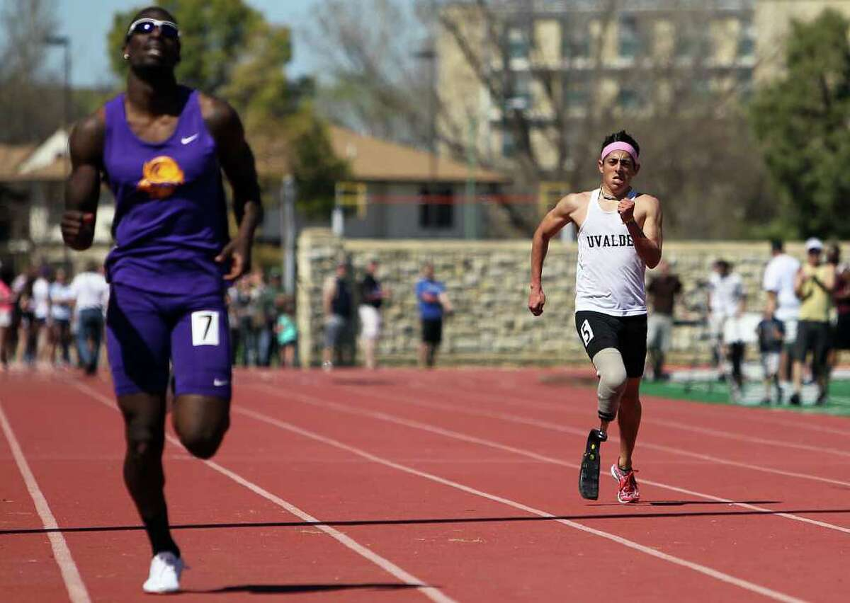 Paralympic Games hopeful James Ortiz (right) runs the 400-meter dash in order to qualify for the U.S. trials competition during the 2012 Alex Francis Classic track and field meet at Fort Hays State University in Hays, Kansas on Saturday, Mar. 24, 2012. Ortiz, who lost a portion of his right leg in an accident in 2006, needed 70 seconds to qualify. He completed the race in 58.36. Kin Man Hui/Express-News.