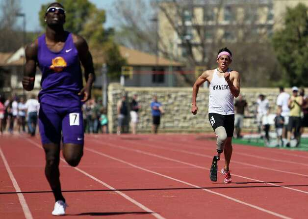 Paralympic Games hopeful James Ortiz (right) runs the 400-meter dash in order to qualify for the U.S. trials competition during the 2012 Alex Francis Classic track and field meet at Fort Hays State University in Hays, Kansas on Saturday, Mar. 24, 2012. Ortiz, who lost a portion of his right leg in an accident in 2006, needed 70 seconds to qualify. He completed the race in 58.36.  Kin Man Hui/Express-News. Photo: KIN MAN HUI, Kin Man Hui/Express-News / ©2012 San Antonio Express-News