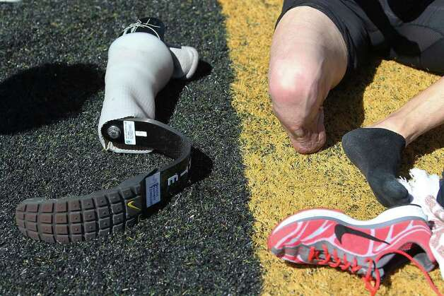 Paralympic Games hopeful James Ortiz removes his running prosthetic after running the 400-meter dash in order to qualify for the U.S. trials competition during the 2012 Alex Francis Classic track and field meet at Fort Hays State University in Hays, Kansas on Saturday, Mar. 24, 2012. Ortiz, who lost a portion of his right leg in an accident in 2006, needed 70 seconds to qualify. He completed the race in 58.36.  Kin Man Hui/Express-News. Photo: KIN MAN HUI, Kin Man Hui/Express-News / ©2012 San Antonio Express-News