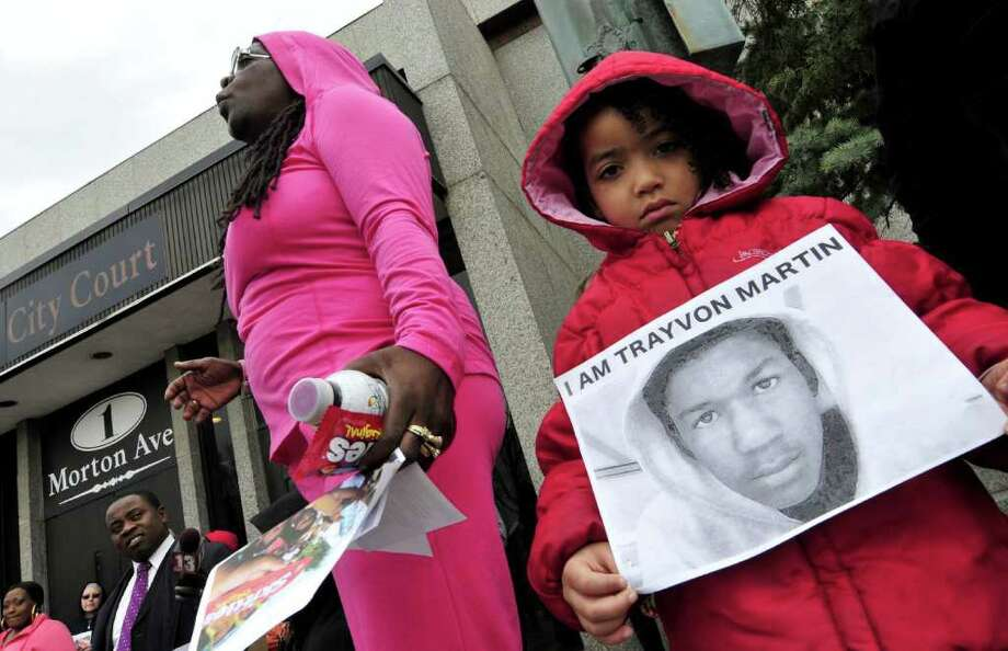 """Corrie Terry, left, speaks as four-year-old Aviell Chairs of Schenectady holds a sign in honor of Trayvon Martin during the """"Hoodies In the Hood March 4 Justice"""" in Albany N.Y., Saturday March 24, 2012. On February 26, Trayvon Martin, 17, who was wearing a hoodie, was shot dead in Florida after being confronted by a neighborhood watch captain.   (Michael P. Farrell/Times Union) Photo: Michael P. Farrell"""
