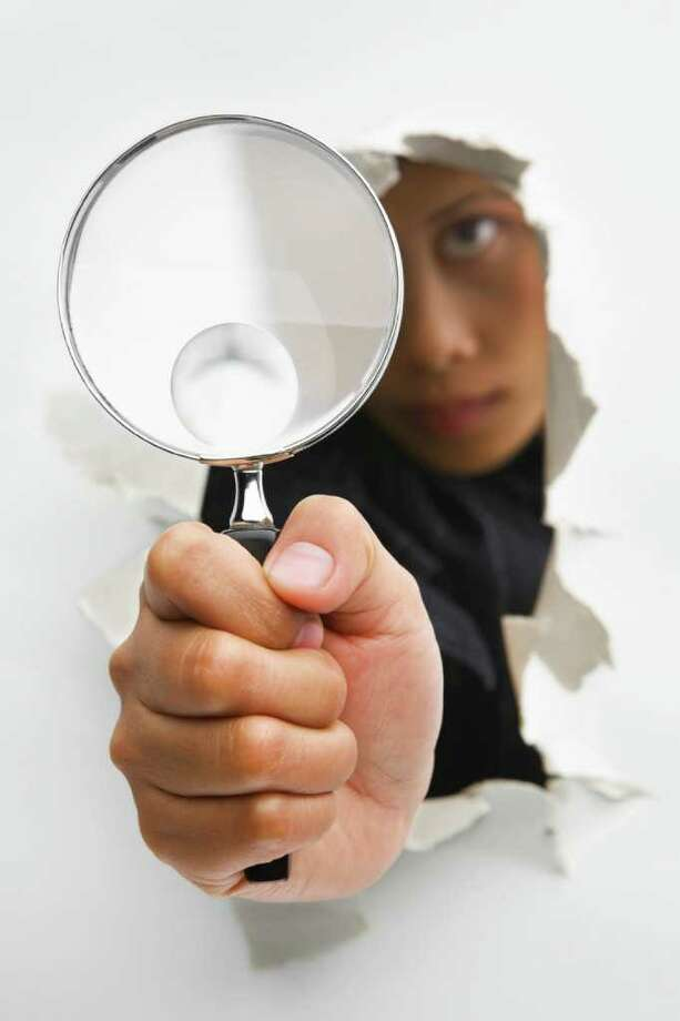 Detective holding magnifying glass from cracked wall means breakthrough in investigation - one of the breakthrough series. PS : focus on the magnifying glass Photo: Rudyanto Wijaya / ©Rudyanto Wijaya