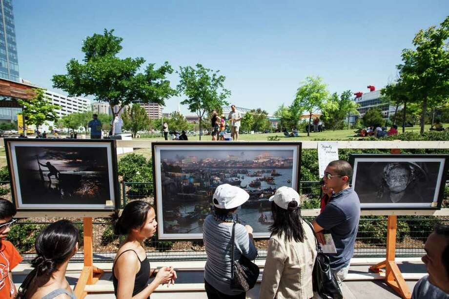 People gather around photos of Vietnam taken by photographer Nhan Nguyen. Photo: Michael Paulsen, Houston Chronicle / © 2012 Houston Chronicle