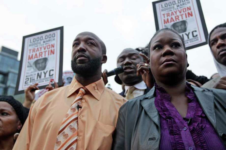 Trayvon Martin's parent's Tracy Martin, left, and Sybrina Fulton, right, take part in the Million Hoodie March in Union Square Wednesday, March 21, 2012 in New York. The march was in memory of Trayvon Martin, a black teenager shot to death by a Hispanic neighborhood watch captain in Florida. The teenager was unarmed and was wearing a hoodie. (AP Photo/Mary Altaffer) Photo: Mary Altaffer