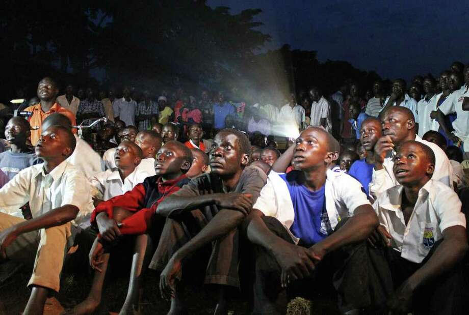 "Ugandans in Lira watch ""KONY 2012,"" a YouTube video about a rebel leader's brutality. Lira was one of the areas ravaged by Joseph Kony's Lord's Resistance Army. Photo: STRINGER / AFP"