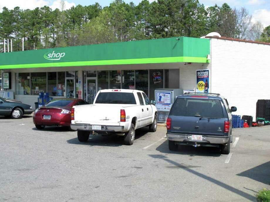 Several cars with North Carolina license plates are parked at the Lake Wylie Minimart in Lake Wylie, S.C. on Wednesday, March 21, 2012. The store's owner thought his business was in South Carolina, but surveyors have determined it is actually in North Carolina, meaning his gas prices will likely go up 30 cents and he can't sell fireworks. (AP Photo/Jeffrey Collins) Photo: Jeffrey Collins / AP