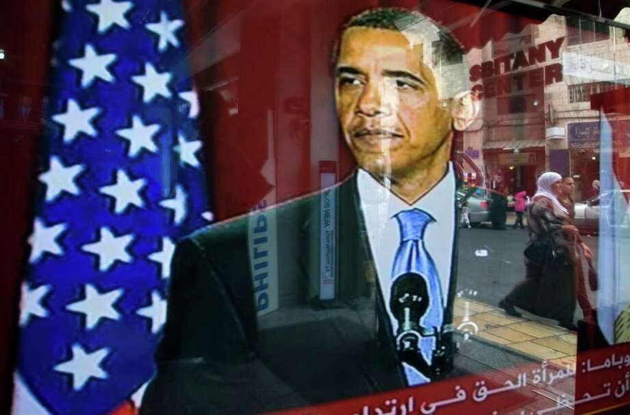 FILE - In this Thursday, June 4, 2009 file photo, Palestinians are reflected in a television screen in a shop window outside Jerusalem's Old City showing U.S. President Barack Obama calling for a new beginning between the United States and Muslims, during his speech delivered at Cairo University. Foreign policy experts in nine countries on five continents, shared their thoughts with The Associated Press, agreeing that the U.S. stands alone as a global superpower, yet perceiving an array of weaknesses that could undermine its stature as numerous emerging powers seek a bigger role on the world stage. (AP Photo/Sebastian Scheiner) Photo: Sebastian Scheiner
