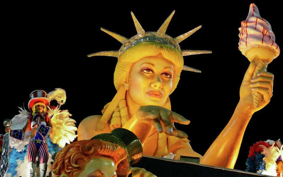 FILE - In this Monday, Feb. 20, 2012 file photo, a dancer performs on a float with a caricature of the Statue of Liberty during the Sao Clemente samba school carnival parade at the Sambadrome in Rio de Janeiro, Brazil. Foreign policy experts in nine countries on five continents, shared their thoughts with The Associated Press, agreeing that the U.S. stands alone as a global superpower, yet perceiving an array of weaknesses that could undermine its stature as numerous emerging powers seek a bigger role on the world stage. (AP Photo/Victor R. Caivano) Photo: Victor R. Caivano