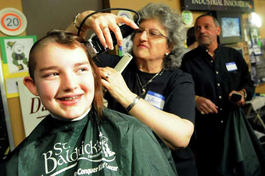 Kira Whisenhunt, 12, of Niskayuna, left, gets her head shaved from JoAnn Vendetti of David's Hair Salon to benefit St. Baldrick's Foundation on Saturday, March 24, 2012, at Proctors Theatre in Schenectady, N.Y. Kira, who raised $2,500 for the cause, said her sixth-grade teacher, Mike Pletman, inspired her. (Cindy Schultz / Times Union) Photo: Cindy Schultz / 00016440A